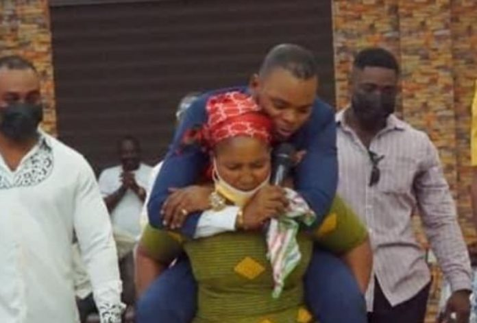 Obinim is back; a woman carries him at her back to get healed of waist pains